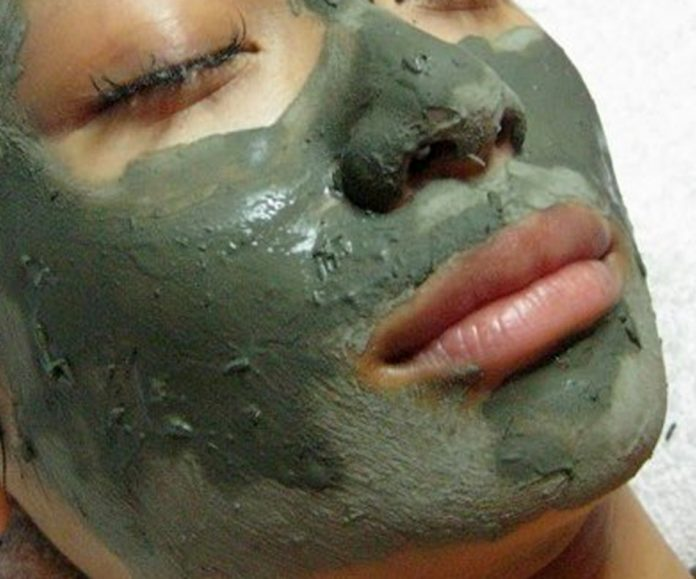 woman using a clay facial mask
